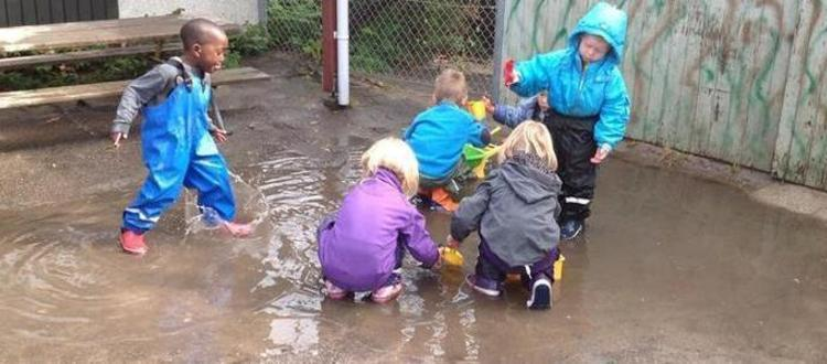 Fem børn leger i stor vandpyt