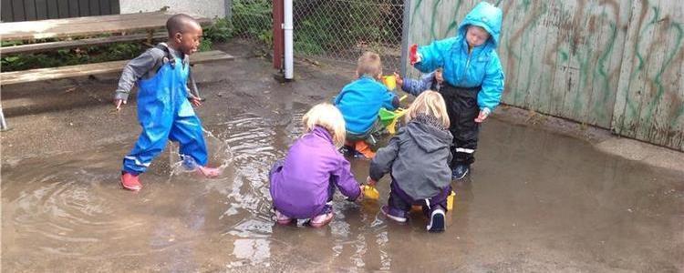 Børn leger i vand efter oversvømmelse