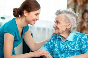 Marte Meo terapeut. Billede af omsorgsassistent og ældre beboer på plejecenter. Marte Meo Uddannelsen.