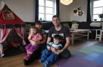 Marte Meo Familiekurser hjælper småbørnsfamilier med at få god kontakt med børnene. far og mor sidder på gulvet med hvert sit barn i skødet.