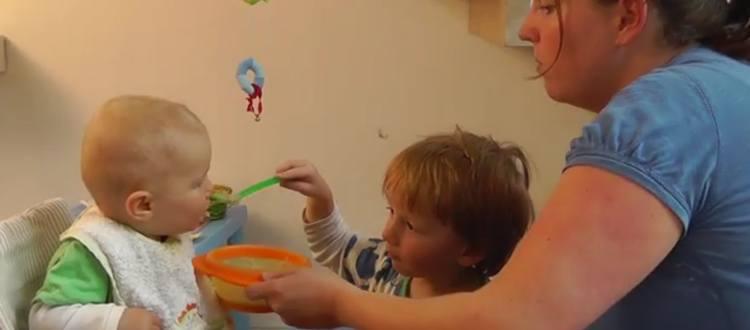 Storebror giver lillebror mad med ske. Mor holder tallerken. Se artiklen koden til at opdrage børn.